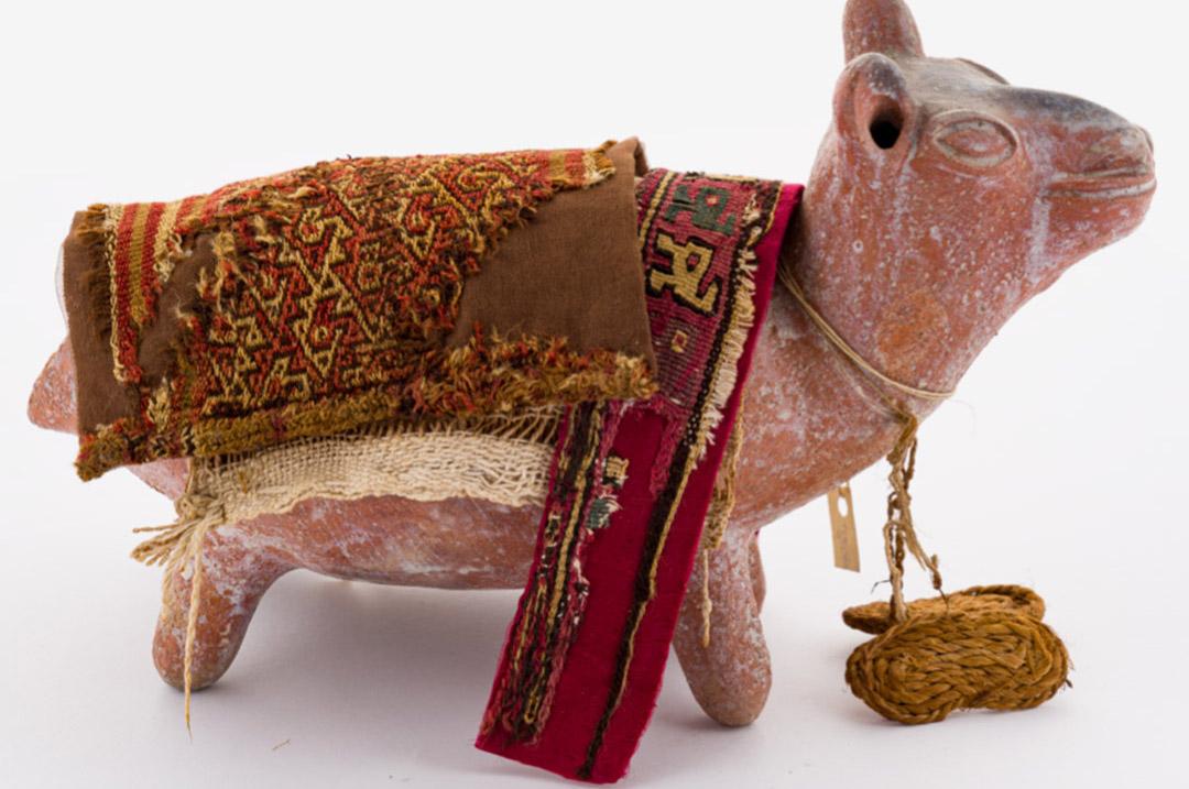 Lama in ceramica, con tessuti sulla groppa e paio di sandali al collo.